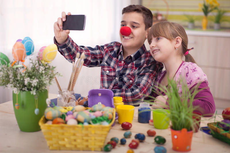 Boy and girl taking selfie at Easter time. Family selfie with easter eggs stock image