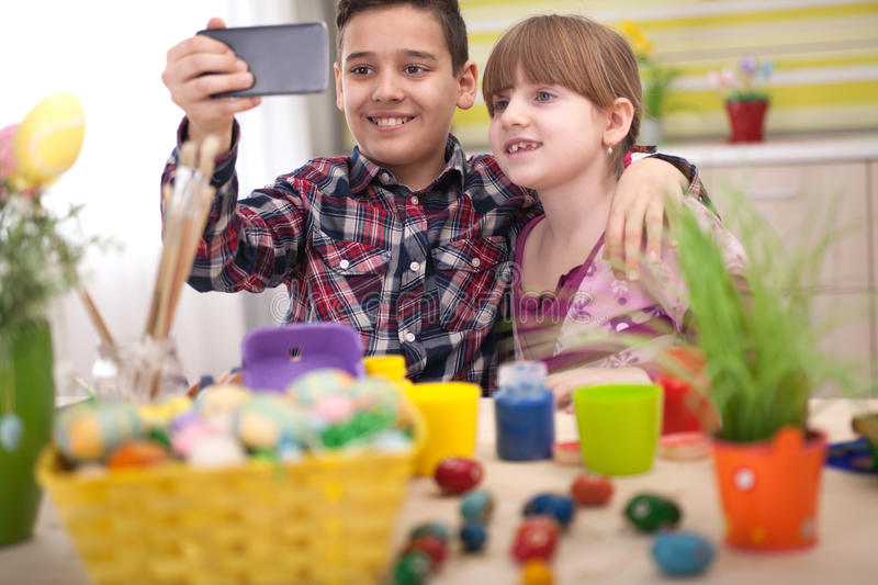 Boy and girl taking selfie at Easter time. Family selfie with easter eggs royalty free stock images