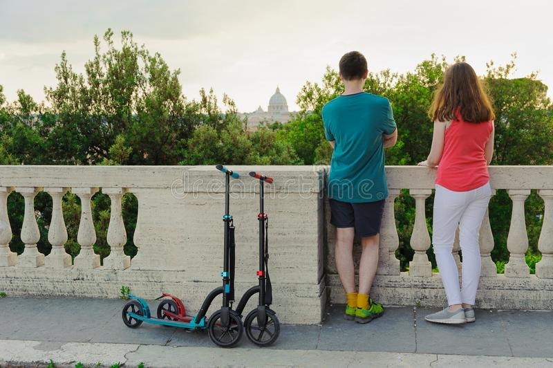 Boy and girl with their push scooters against the backdrop of the Vatican in the park Villa Borghese. Boy and girl with their push scooters against the backdrop royalty free stock photography