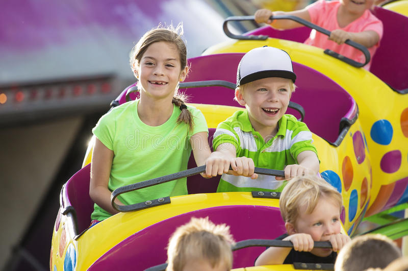 Boy and Girl on a thrilling roller coaster ride at an amusement park stock images