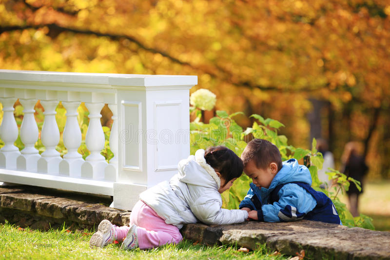 Boy and girl toddlers playing in autumn leaves stock photo