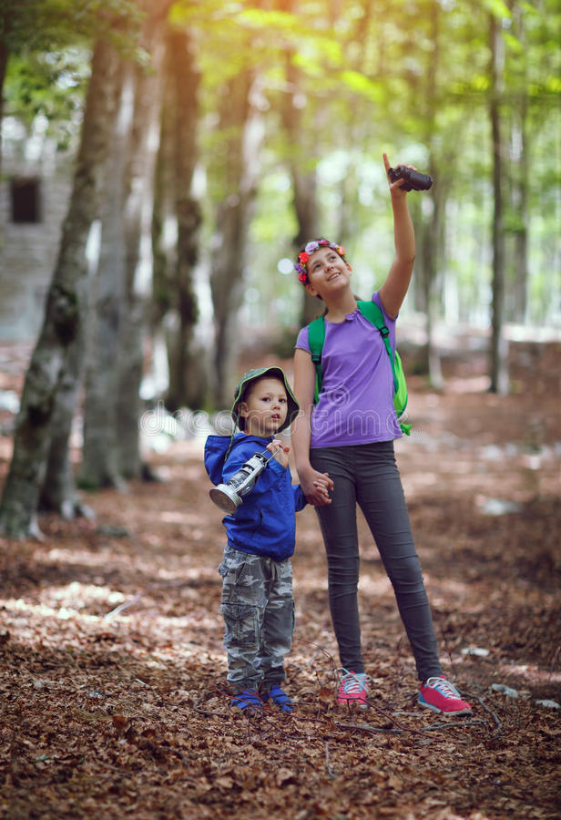 Boy and girl using binoculars and exploring together stock photo