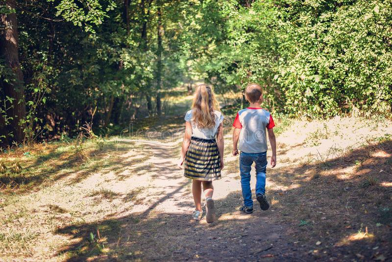 A boy and a girl walk along a path in the forest stock images