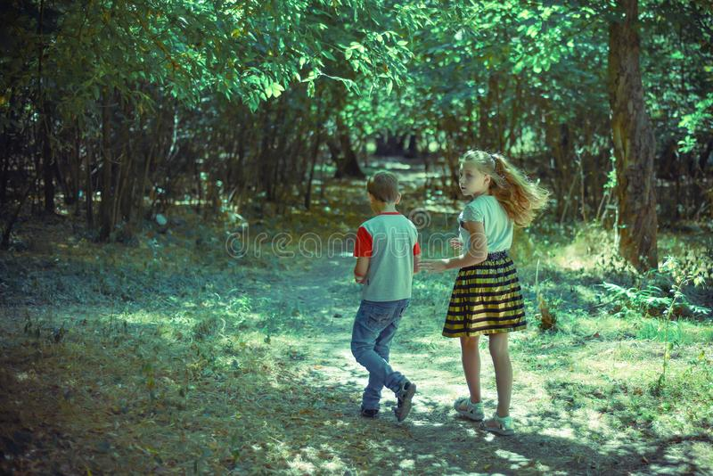 A boy and a girl walk along a path in the forest and look back royalty free stock photography