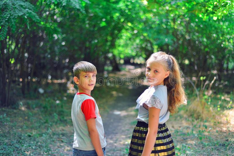 A boy and a girl walk along a path in the forest and look back royalty free stock photo
