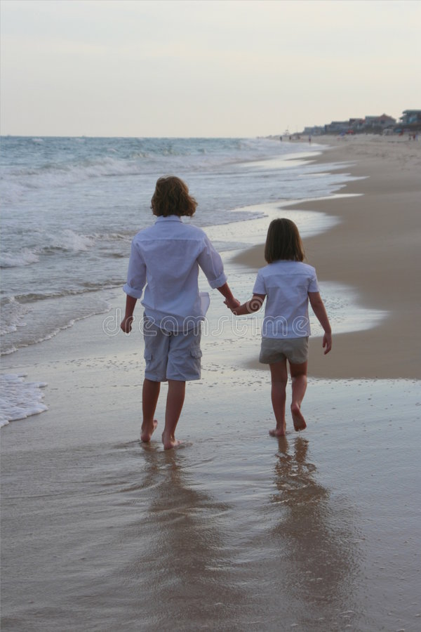 Boy and girl walking on the beach stock image