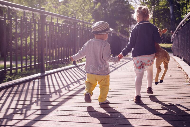 Boy and Girl Walking on Bridge during Daytime royalty free stock images