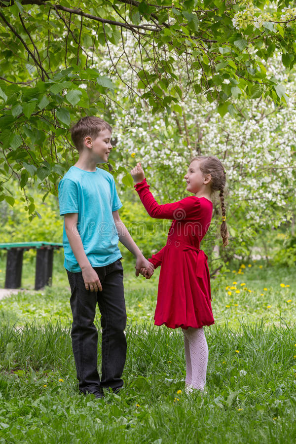 Boy and girl walking in the park royalty free stock photography