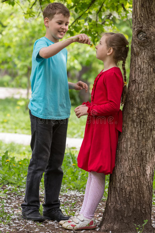 Boy and girl walking in the park stock photos