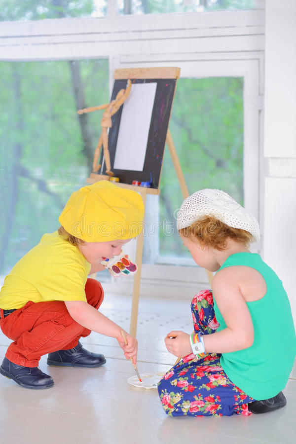Boy and girl with watercolors sit royalty free stock photos