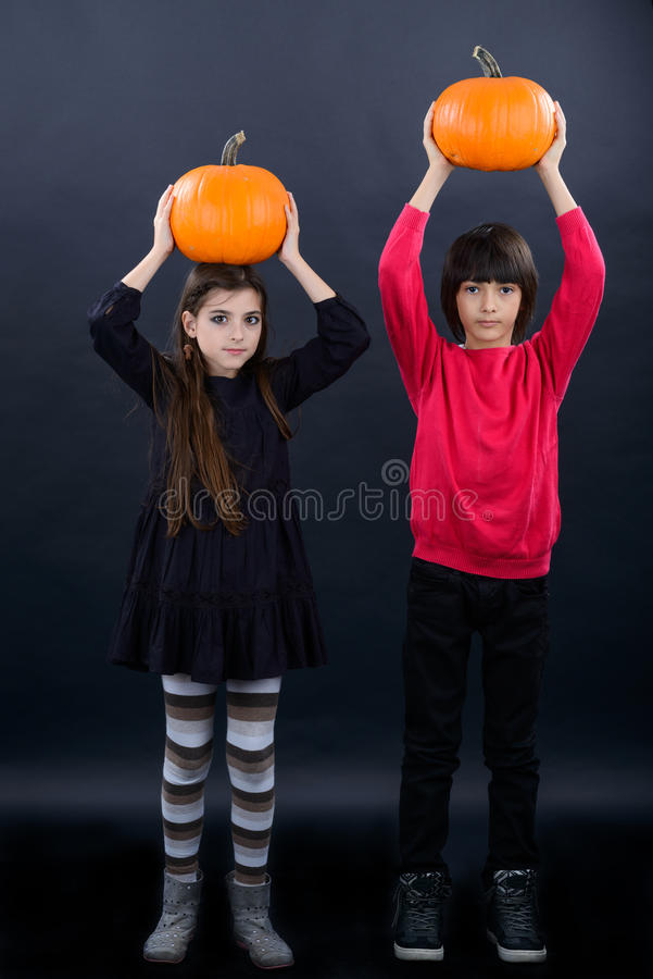 download boy and girl wearing halloween costume with pumpkin on black ba stock image image