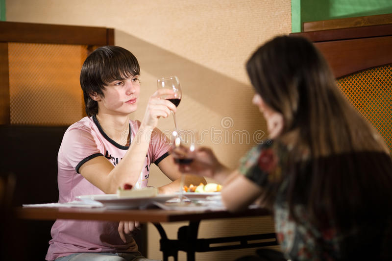 Boy And Girl With Wineglasses  At Table Royalty Free Stock Photography