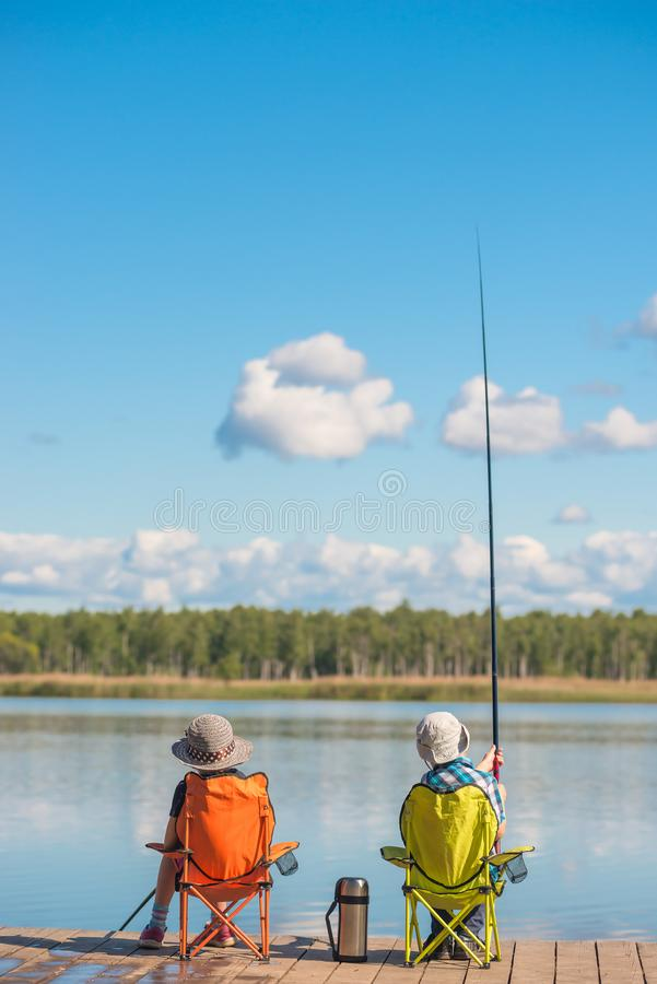 A boy and a girl on a wooden pier are fishing royalty free stock images