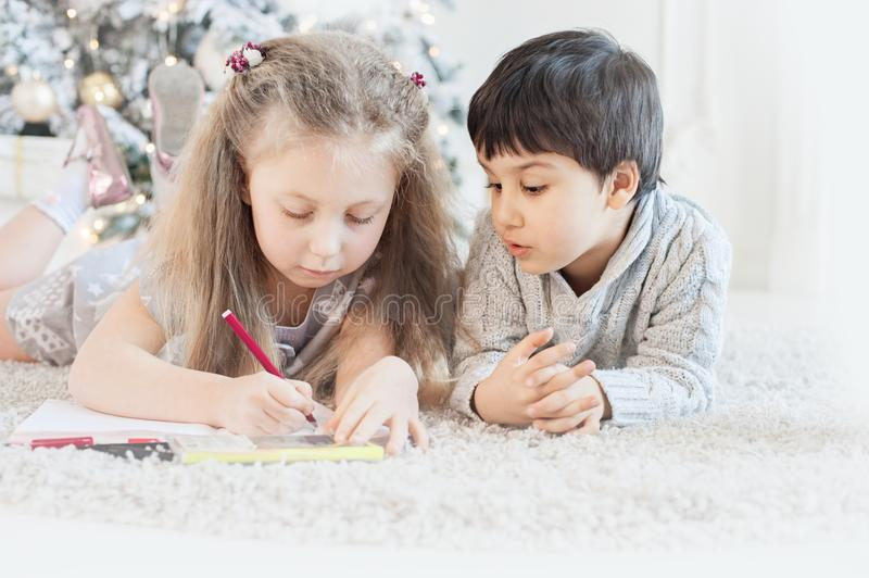 boy and girl write a letter to Santa Claus royalty free stock images