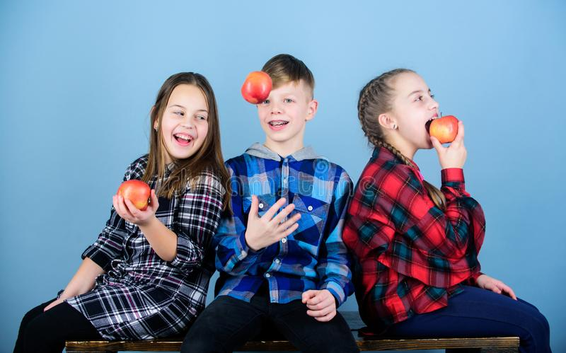 Boy and girls friends eat apple snack while relaxing. Teens with healthy snack. Healthy dieting and vitamin nutrition. School snack concept. Group cheerful stock photos