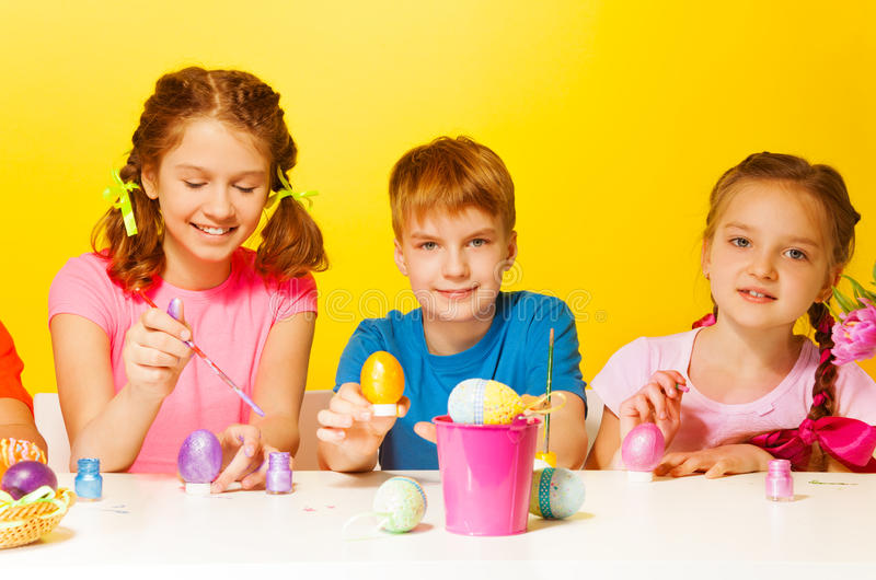Boy and 2 girls painting Easter eggs at the table. On the yellow background royalty free stock images