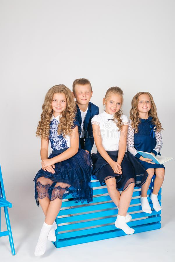 Boy and girls schoolchildren in fashionable school clothes with a school bag and a book. On a white background stock photography
