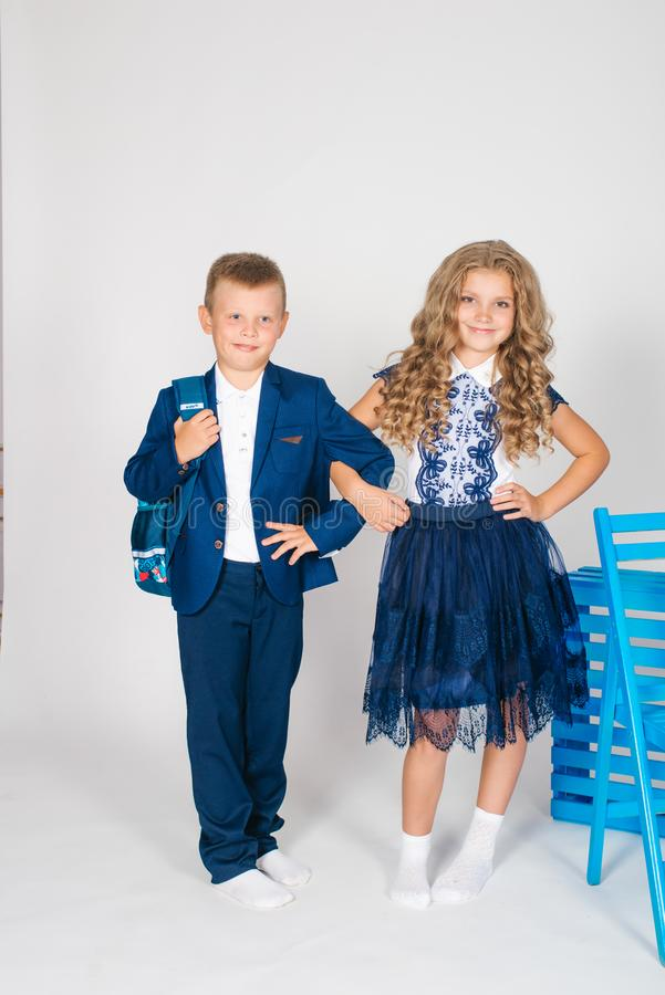 Boy and girls schoolchildren in fashionable school clothes with a school bag and a book. On a white background royalty free stock photography