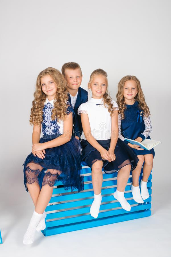 Boy and girls schoolchildren in fashionable school clothes with a school bag and a book. On a white background royalty free stock image