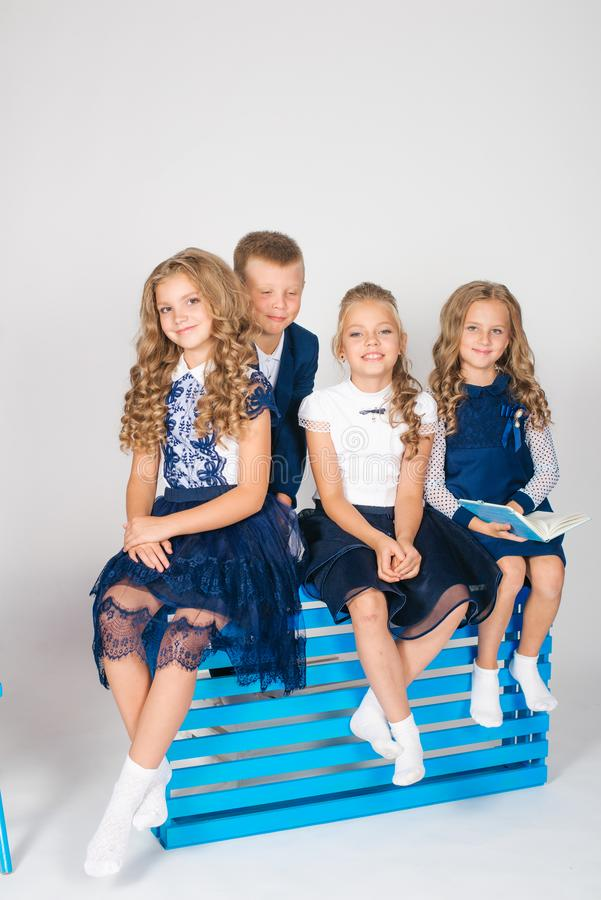 Boy and girls schoolchildren in fashionable school clothes with a school bag and a book. On a white background stock photo