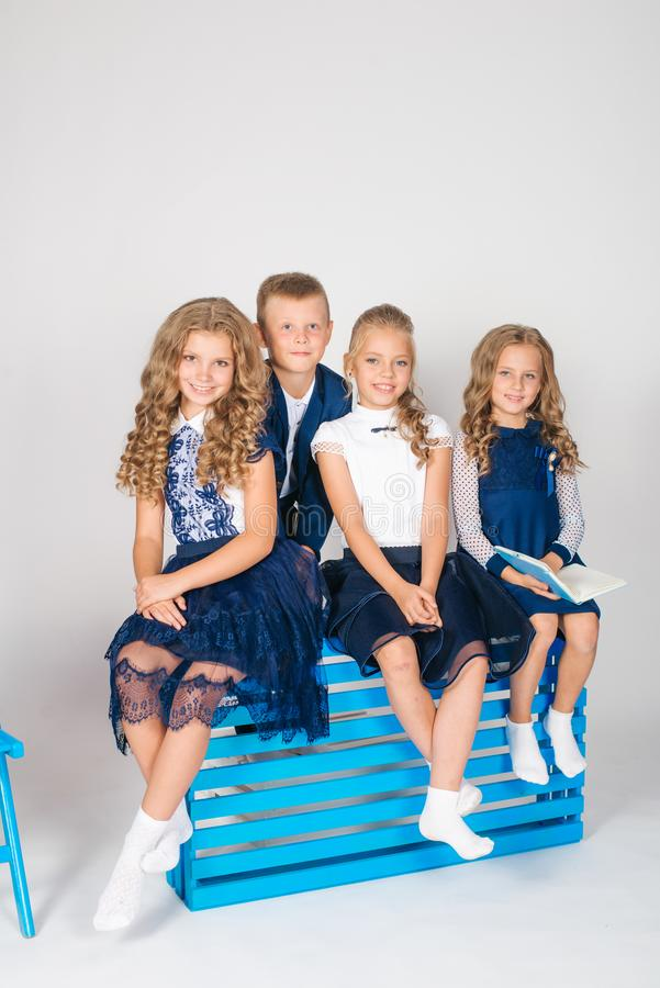 Boy and girls schoolchildren in fashionable school clothes with a school bag and a book. On a white background royalty free stock photos