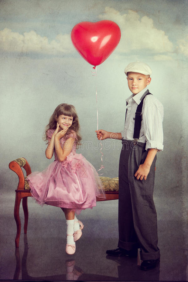 The boy gives a balloon to the girl stock images