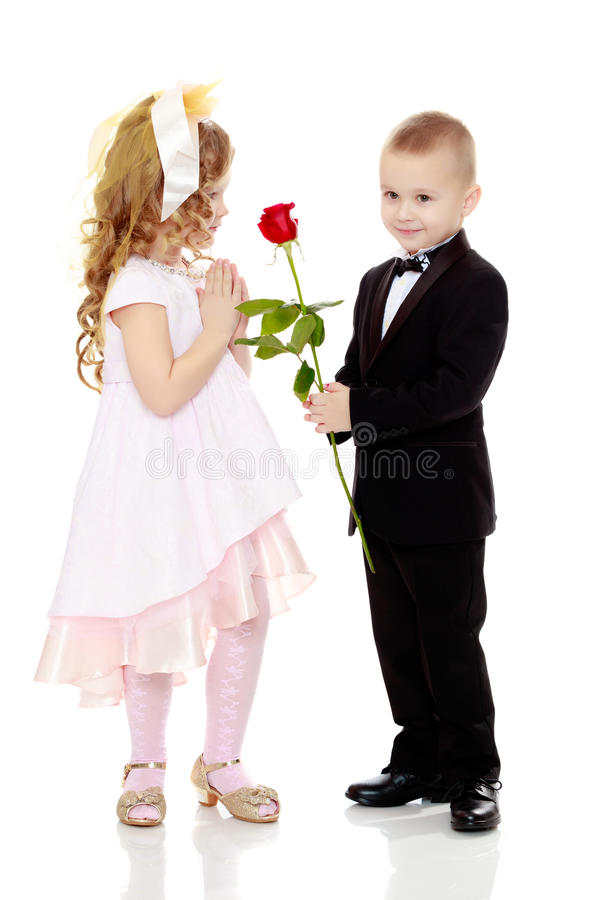 The boy gives the girl a flower. Little boy in black suit with bow tie gives a big red rose charming little girl. Isolated on white background royalty free stock photos