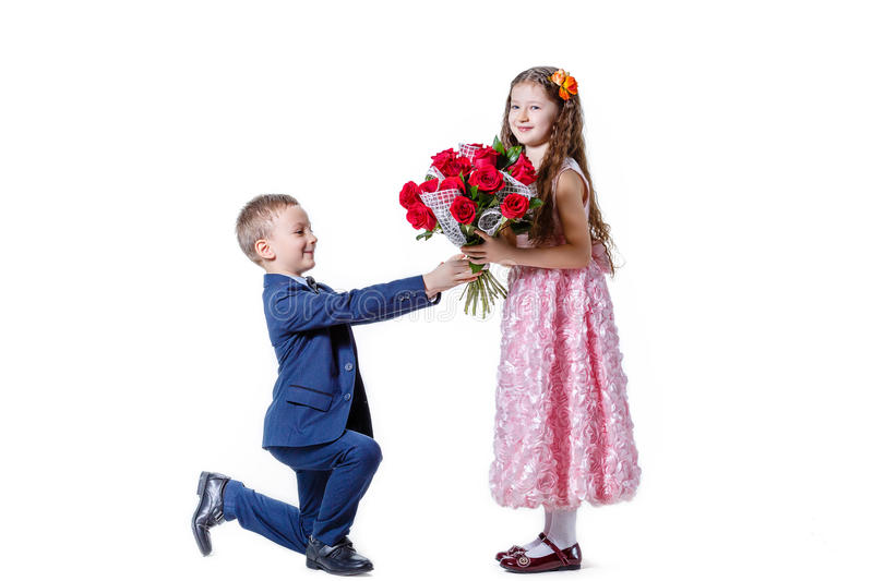 Boy gives a girl flowers on the day of St . Valentine royalty free stock photography