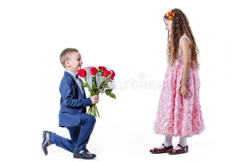 Boy gives a girl flowers on the day of St . Valentine royalty free stock image
