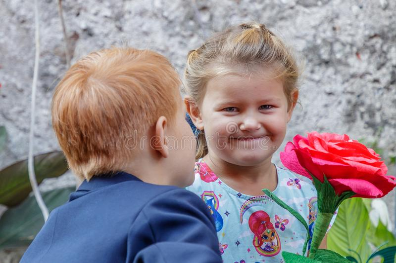 Boy gives girl a red flower stock images