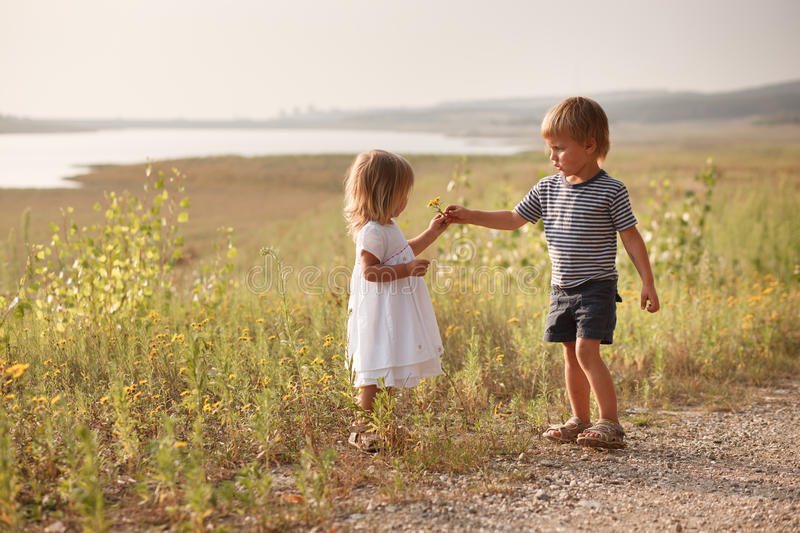 Boy giving bouquet of spring flowers to happy girl. This image has attached release royalty free stock photos
