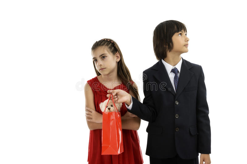 Boy giving a gift to his girlfriend. Shy boy giving a gift to his girlfriend royalty free stock photos