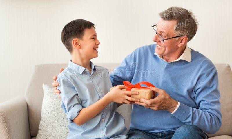 Boy Giving Grandfather Birthday Gift Sitting On Sofa Indoor stock photo