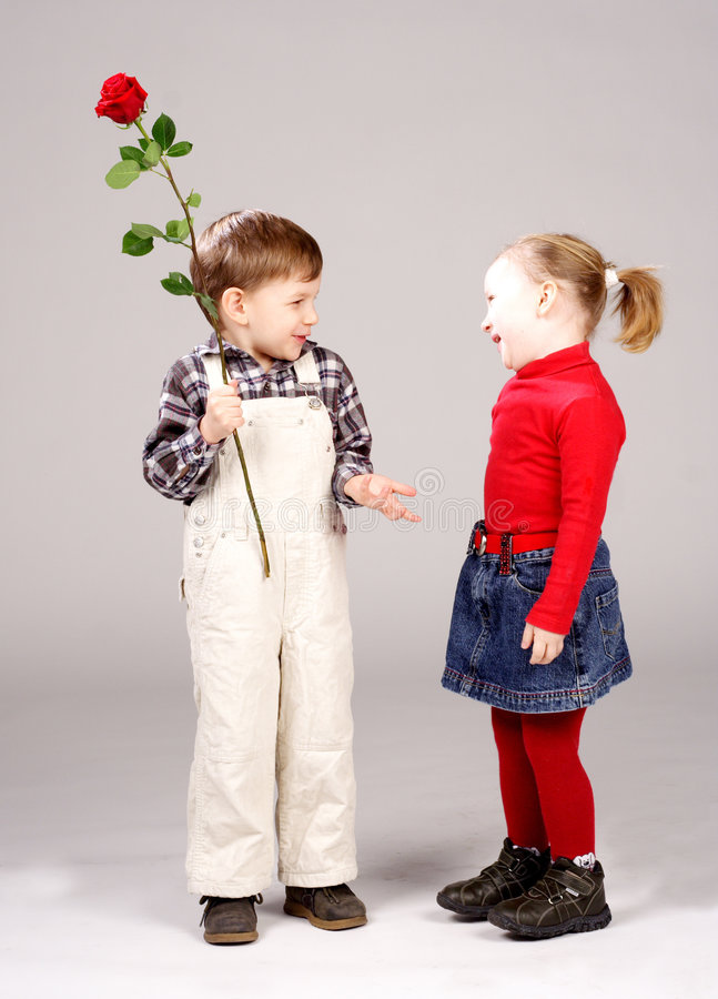 Boy giving preschool girl rose. Cute preschool boy giving happy girl red rose; studio background royalty free stock photo
