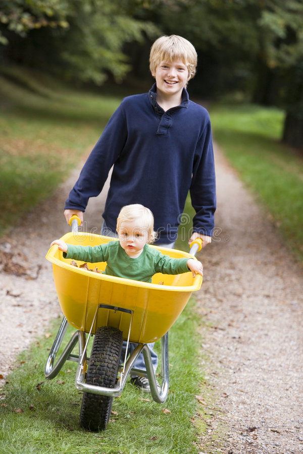 Boy Giving Toddler Ride In Wheelbarrow Stock Image