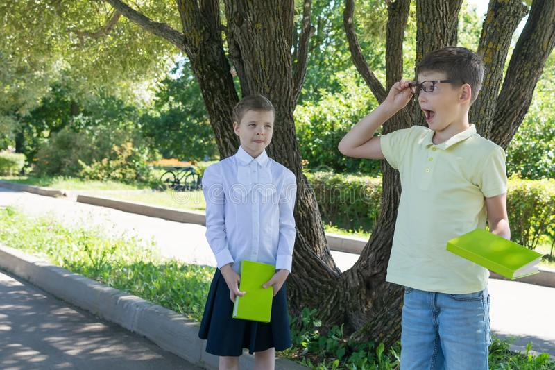 The boy in glasses with a book in his hands was surprised and the girl looks at him stock images