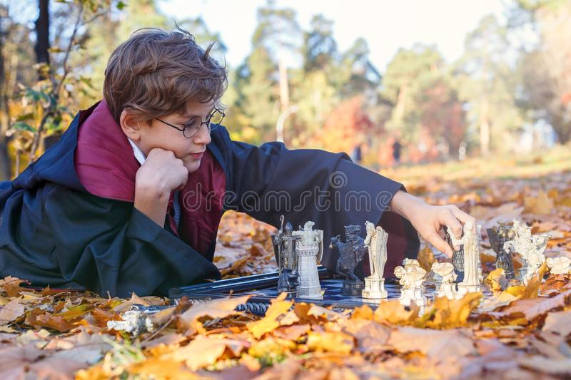 Boy in glasses lies in autumn park with gold leaves, plays chess, makes move, wears in black suit. Kyiv/Ukraine - October 10, 2017: Boy in glasses lies in autumn royalty free stock photography