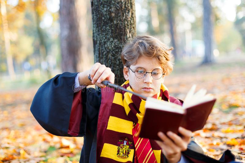 Boy in glasses lies in autumn park with gold leaves, plays chess, makes move, wears in black suit. Kyiv/Ukraine - October 10, 2017: Boy in glasses lies in autumn royalty free stock photo