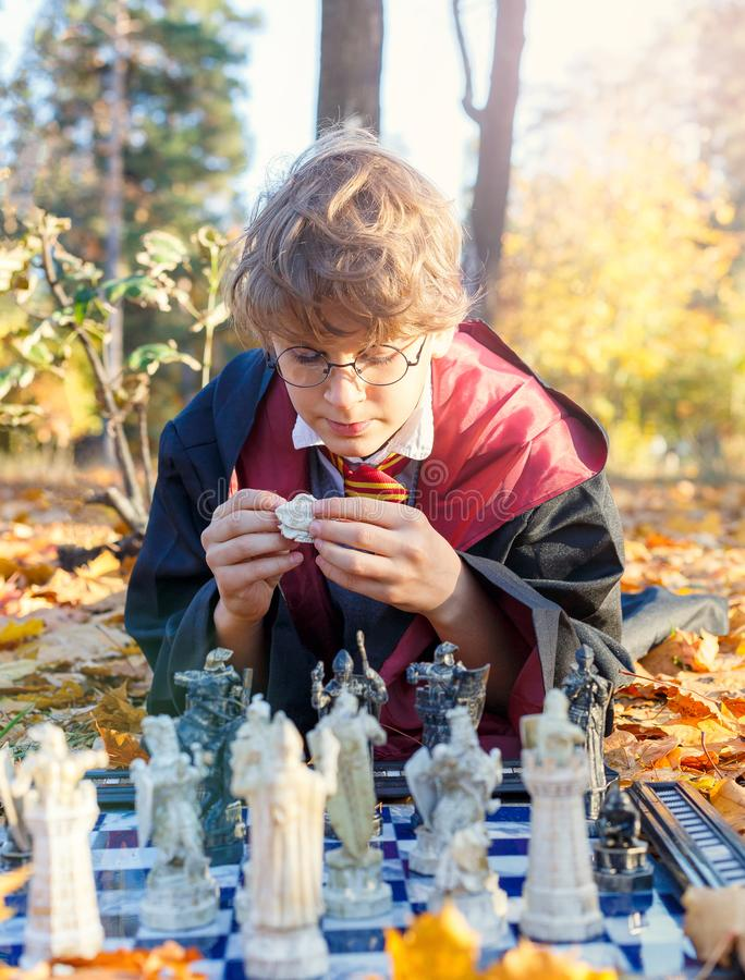 Boy in glasses lies in autumn park with gold leaves, plays chess, makes move, wears in black suit. Kyiv/Ukraine - October 10, 2017: Boy in glasses lies in autumn stock photos