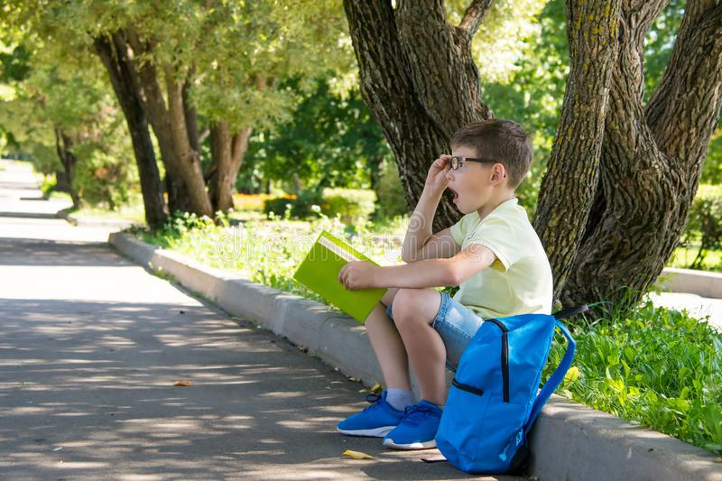 The boy in glasses, in the open air thought about the read stock photography