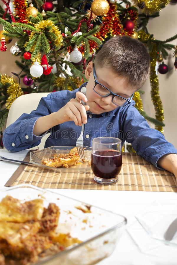 The boy in glasses sits at the table and pokes food on his fork on the plate. A beautifully decorated Christmas tree in the backgr royalty free stock photography