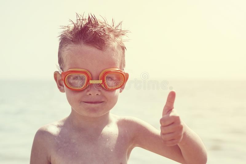 A boy in glasses for swimming shows a thumbs up on the background of the sea. Kid in spectacles for swimming in the sea stock photos