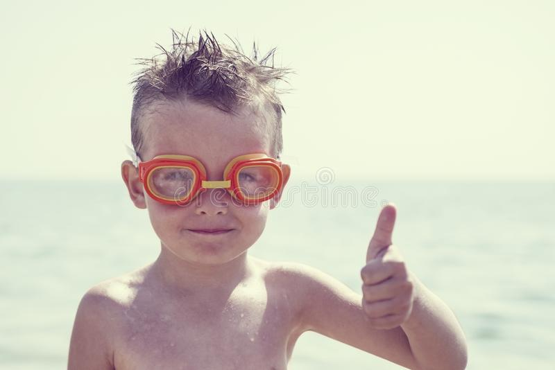 A boy in glasses for swimming shows a thumbs up on the background of the sea. Kid in spectacles for swimming in the sea stock photography