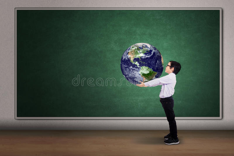 Boy with a globe of the world. On the classroom royalty free stock photos