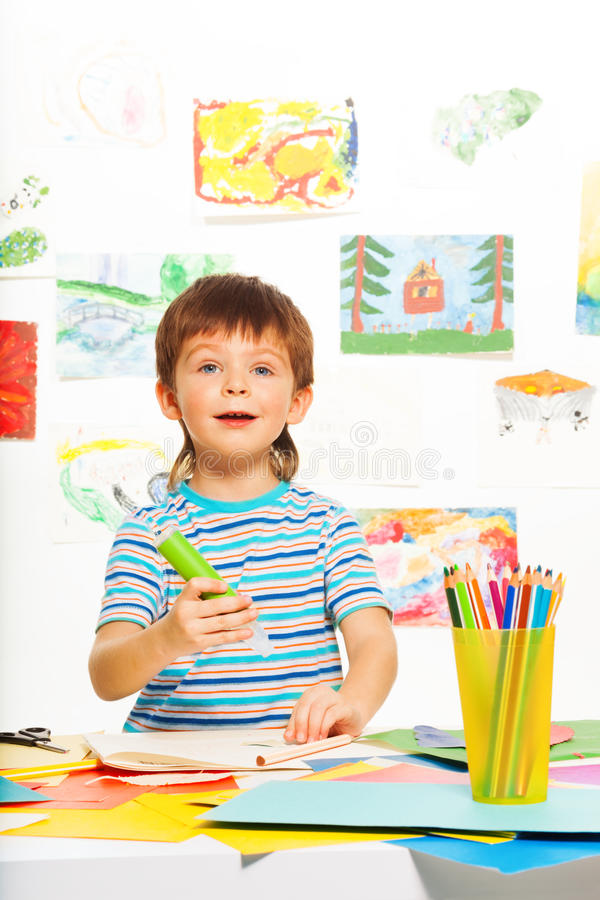Boy with glue stick and pencils. Boy in early development class cut paper and glue stick with images on the wall on background royalty free stock photo