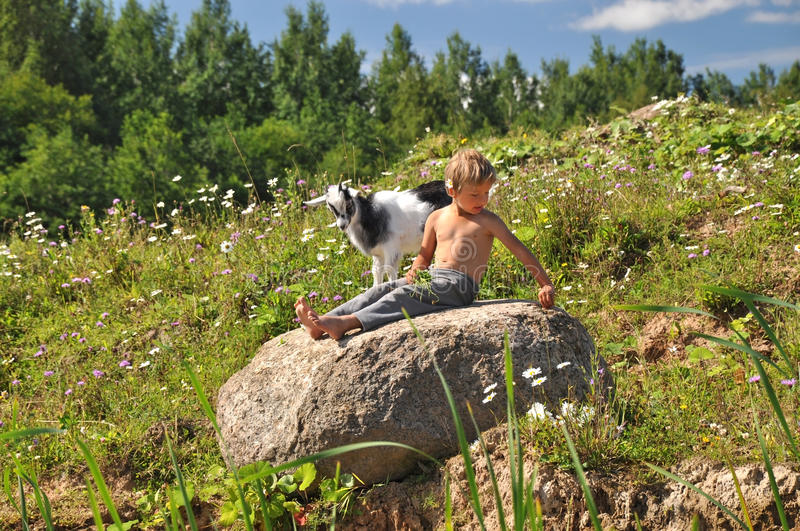 Boy and goat playing on a stone royalty free stock photography