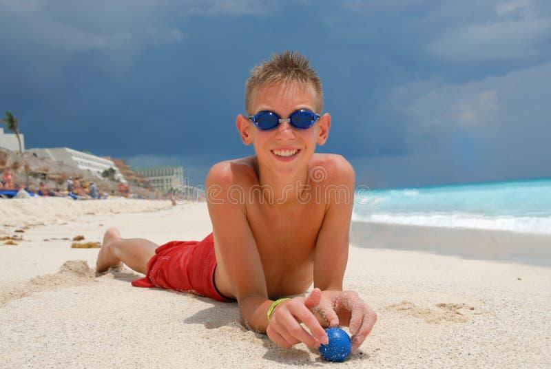 Boy with goggles on beach stock photos