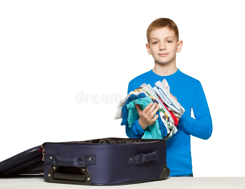 Boy going pack his luggage bag with clothes. Boy going travelling packing luggage bag with clothes royalty free stock photography