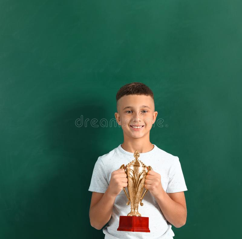 Boy with golden winning cup on near chalkboard. Happy boy with golden winning cup on near chalkboard royalty free stock images