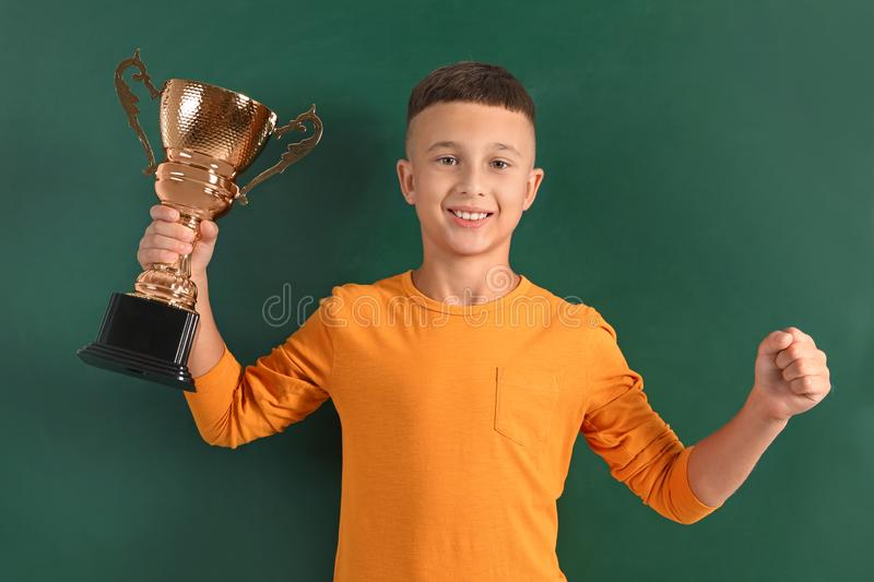 Boy with golden winning cup on near chalkboard. Happy boy with golden winning cup on near chalkboard royalty free stock photos